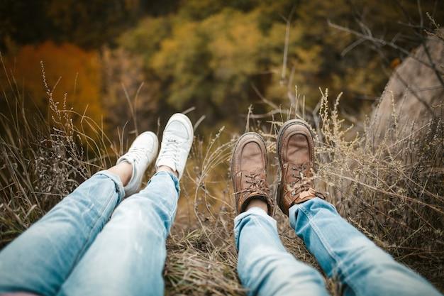 Молодой человек и женщина сидят на краю, опуская ноги