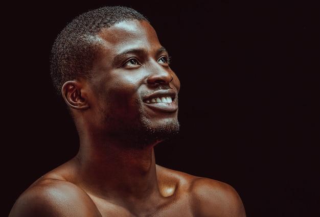 Студия улыбки человека чёрного африканца в красивом стиле на черной предпосылке.