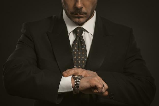 Бизнесмен, проверка времени на его наручные часы. крупным планом портрет деловой человек, глядя на часы в наличии.