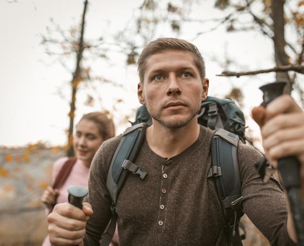 Человек смотрит вперед, опираясь на походные бассейны. семья с рюкзаками гуляет вместе по осеннему лесу