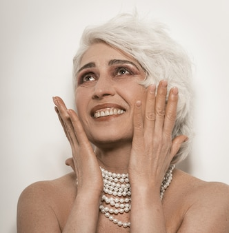 白で隔離される歯を見せる笑顔の年配の女性のヌード