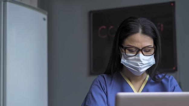 Утомленный женский доктор работает на компьютере сидя на столе в ее офисе.