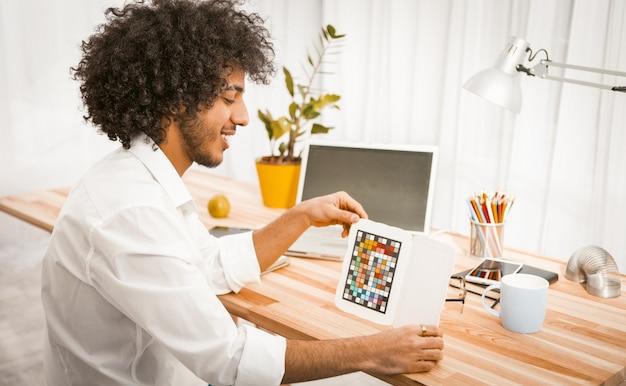 Творческий бизнесмен держит контролер цвета или специальную цель для регулировки цвета во время работы от домашнего ноутбука.