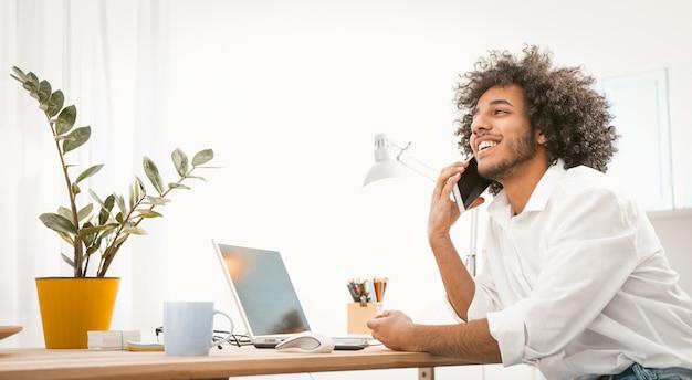 Улыбающийся деловой человек разговаривает по телефону. молодой человек ведет онлайн переговоры на мобильном телефоне