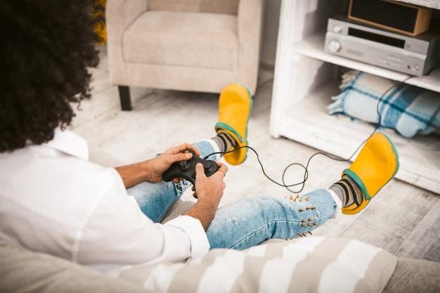 Молодой человек играет в компьютерную игру.
