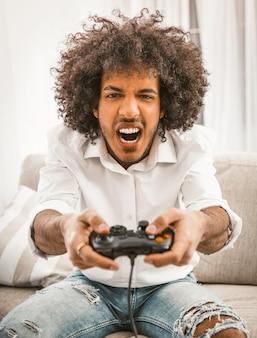Кричащий геймер стреляет или атакует в компьютерной игре.