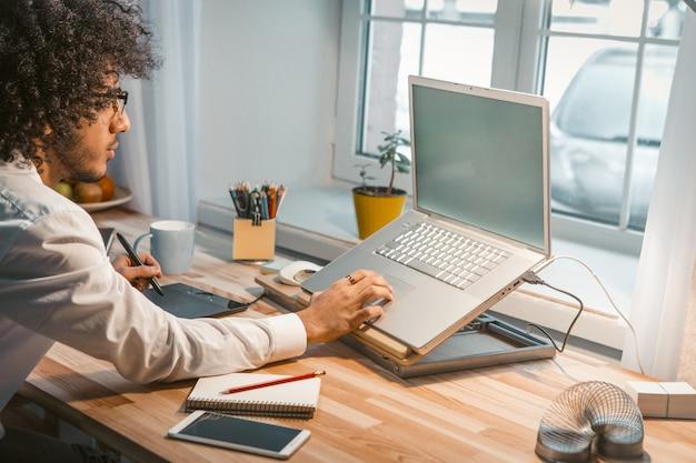 若いデザイナーが自宅でノートパソコンとグラフィックタブレットを使用しています。アラビア語のビジネスの男性は家から働いています。フリーランスのコンセプト