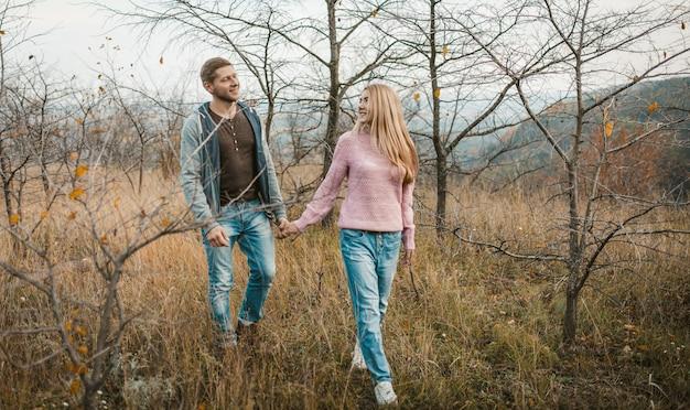 男と女が自然の中で一緒に屋外を歩きます。恋をしている二人が手を繋いで丘の中腹を歩いている