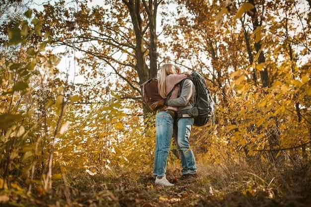 秋の自然を眺めながら、旅行者の愛するカップルが抱擁します。若い人たちは、多色の秋の自然の中で抱きしめています。下から撮影。愛とハイキングのコンセプト