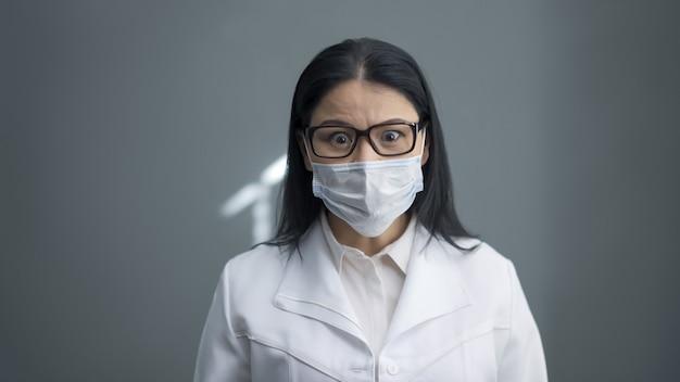 Обеспокоенный доктор смотрит в камеру. удивленная взволнованная молодая женщина в защитной маске и белой униформе на сером фоне