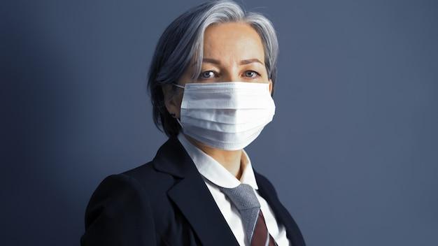 マスクの深刻な灰色の実業家。カメラを見て白人の中年の肖像画を間近します。両側にテキストスペース。トーンのイメージ。ビジネスコンセプトです。検疫の概念