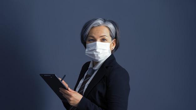 デジタルメモ帳を使用して防護マスクで自信を持って中年女性実業家。灰色の女性モデルはスタジオで灰色の背景に分離されたカメラを見てください。トーン画像