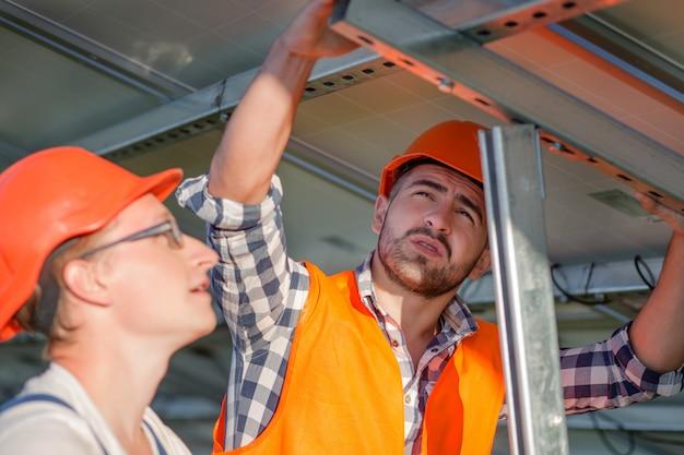 Инженеры, устанавливающие солнечные батареи на раме.