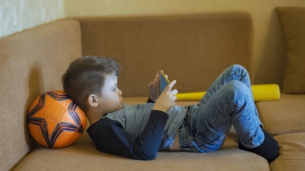 スマート携帯電話でゲームをしている少年