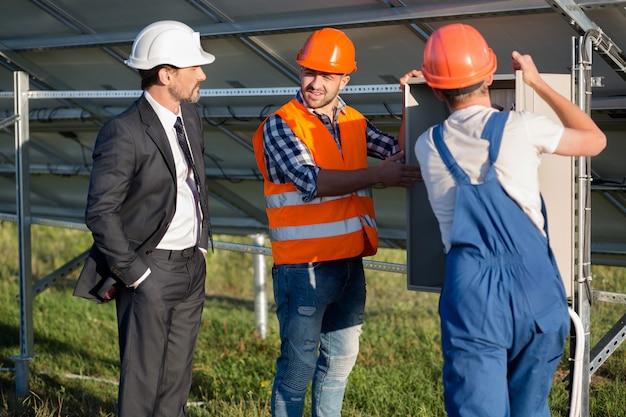Инженеры, предлагающие бизнес-клиенту посмотреть на электрическую коробку.
