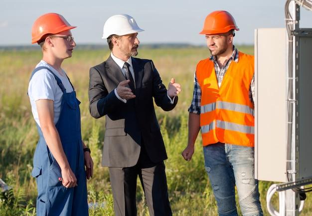 太陽電池パネルの作業工程を従業員に説明する実業家。