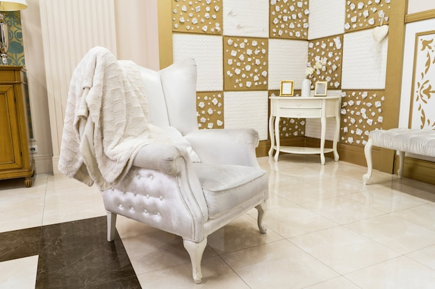 Роскошный интерьер дома в светлых тонах с красивым белым стеганым креслом