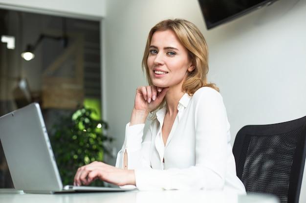 自信を持ってビジネスの女性がオフィスのコンピューターでの作業