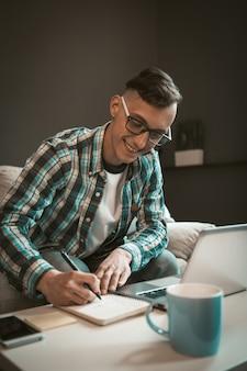 ホームオフィスでのプロジェクトに取り組んで幸せなフリーランスの男の肖像画。フリーランスでのリモート作業の現代的なコンセプト。