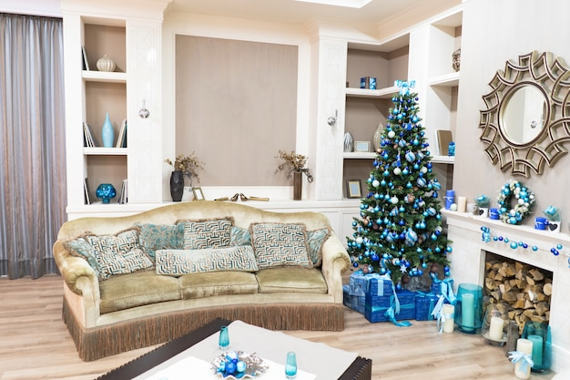 コーナーのクリスマスツリーと美しい新年のインテリア。枕とソファーと緑のクリスマスツリーが美しいプレゼント。甘い家の快適さ。