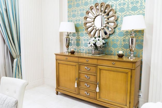 Стильный интерьер дома в винтажном стиле с деревянным комодом и украшенным зеркалом. симметричные лампы для чтения на комоде. стильный дизайн дома.