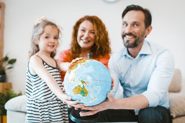 Мама, папа и маленькая девочка, планируя отпуск, держа глобус.
