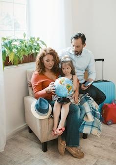 Счастливая семья сидя на кресле изучая глобус.
