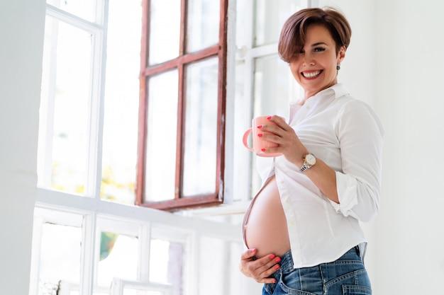 妊娠中の女性が屋内で胎児の笑顔を待っています
