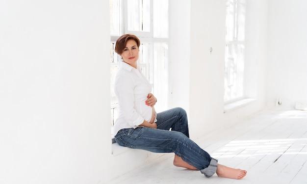 Счастливая беременная женщина, сидя в белой комнате