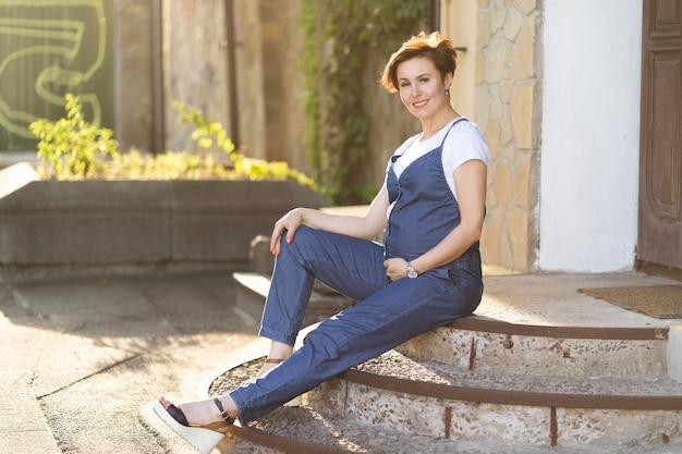 屋外の階段に座っている青いジャンプスーツで妊娠中の女性