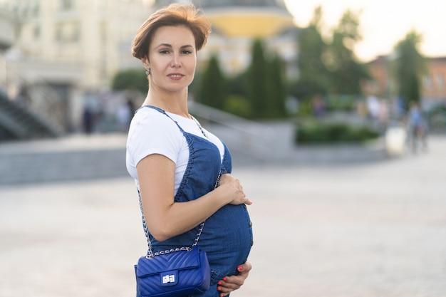 Беременная женщина в синей одежде на улице