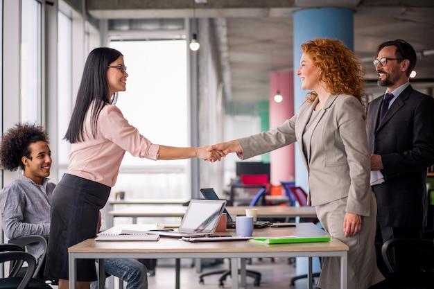 Две деловые женщины пожимают друг другу руки.
