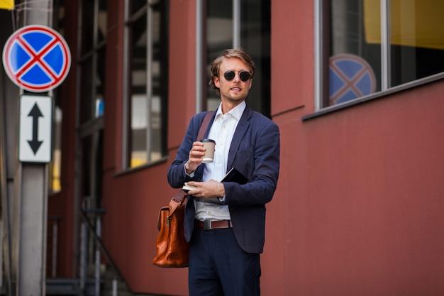 Привлекательный мужчина в формальной одежде и солнцезащитных очках наслаждается кофе на улице возле офиса