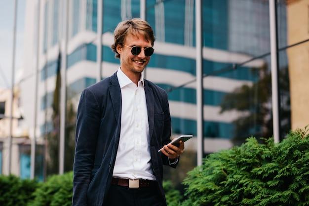 美しいスタイリッシュなスーツを着た中年のマネージャーが、職場での昇進についての肯定的なニュースを電話で受け取る