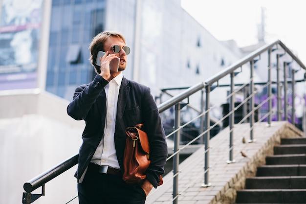 Менеджер получил телефонный звонок, когда он спешил на работу на улице