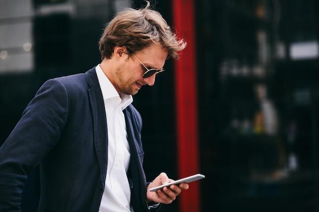 スタイリッシュな若い男性の上司は、駐車場に立っている間彼の携帯電話をチェックします