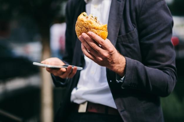 ハンバーガーとビジネスマンのクローズアップショットの手で携帯電話。