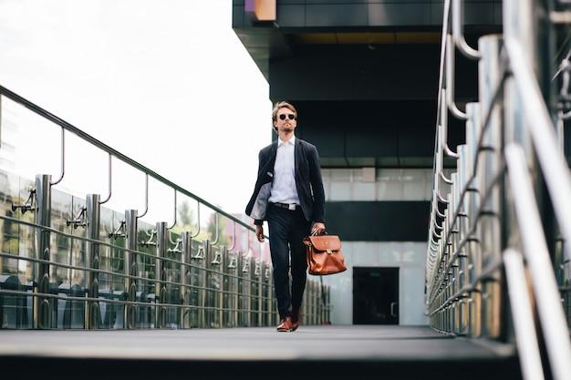 Босс в костюме и солнцезащитных очках с портфелем в руке приступает к работе