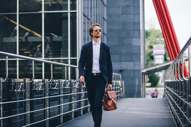 メガネとオフィススーツを持った魅力的なビジネスマンが路上で仕事に出かけた
