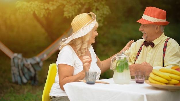 老夫婦の幸せな関係。笑顔の小さな祖父母がテーブルに座って、若者の思い出について話している。庭でフルーツとレモネードを飲む