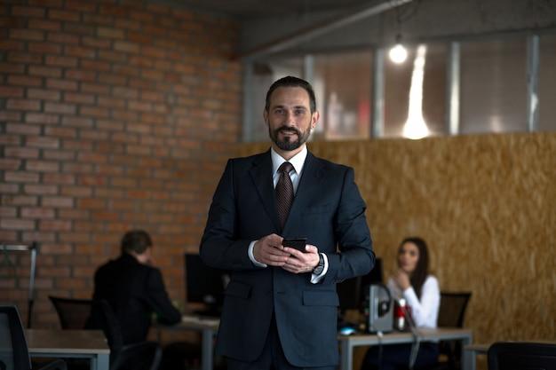オフィスで働くハンサムな若い笑顔実業家
