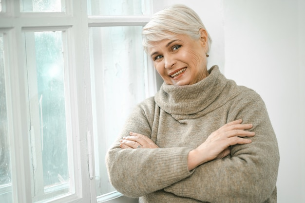 Седая старшая женщина стоит у окна и смотрит в сторону
