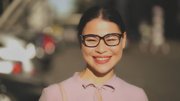 Брюнетка средних лет в очках радостно смеется в солнечный день