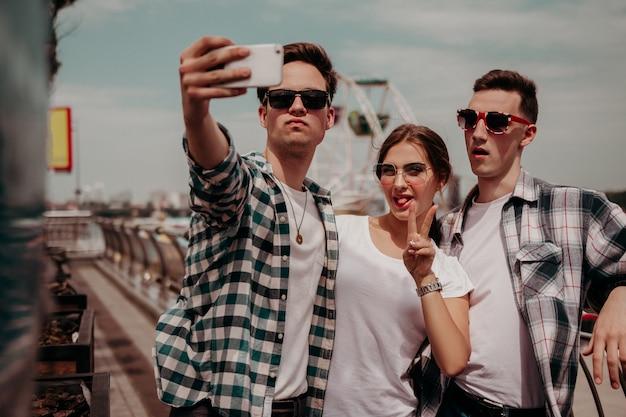Группа молодых людей делает селфи во время летней прогулки по городу