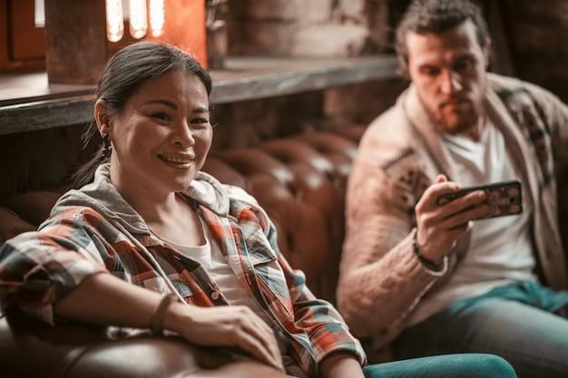 Друзья сидят на диване и смотрят на мобильный