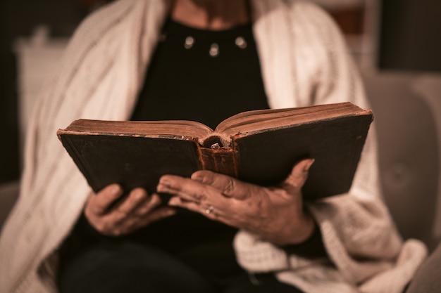 年配の女性は彼女の手でアンティークの本を保持します