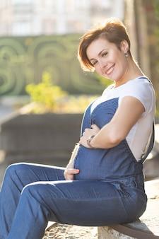 Улыбающаяся беременная женщина средних лет, сидящая на ступеньках на улице