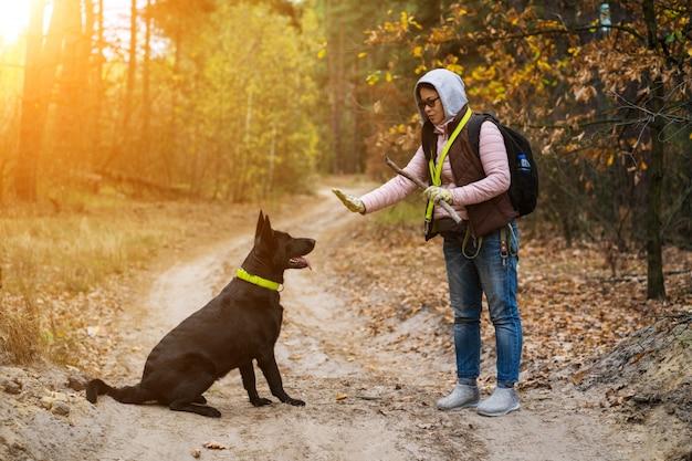 Женщина дрессирует собаку во время прогулки в лесу