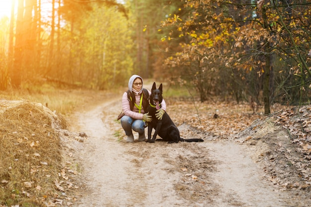 森を歩きながら犬を抱擁する女性