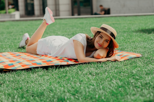 Девушка в соломенной шляпе расслабленной на коврике в парке.